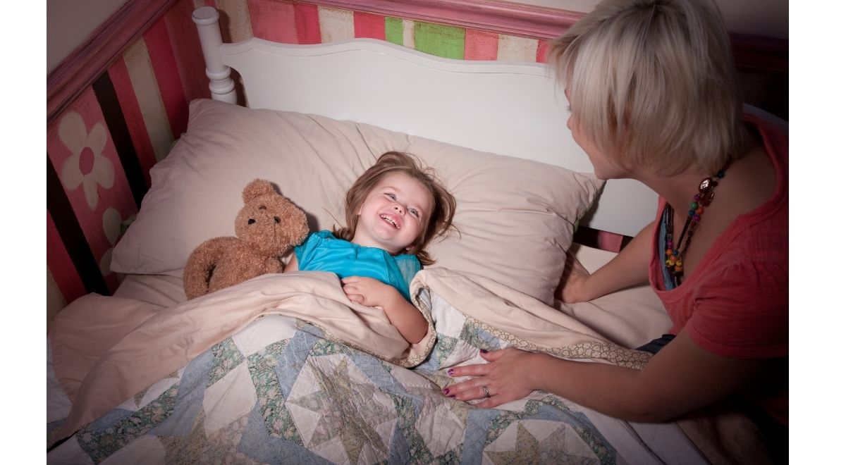 child being tucked into bed by a woman