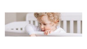 close up of a baby with blonde curls leaning over the front of the crib head banging