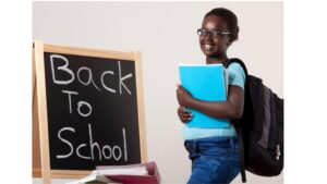"""A girl standing in front of a chalkboard that says """"back to school"""" on it"""