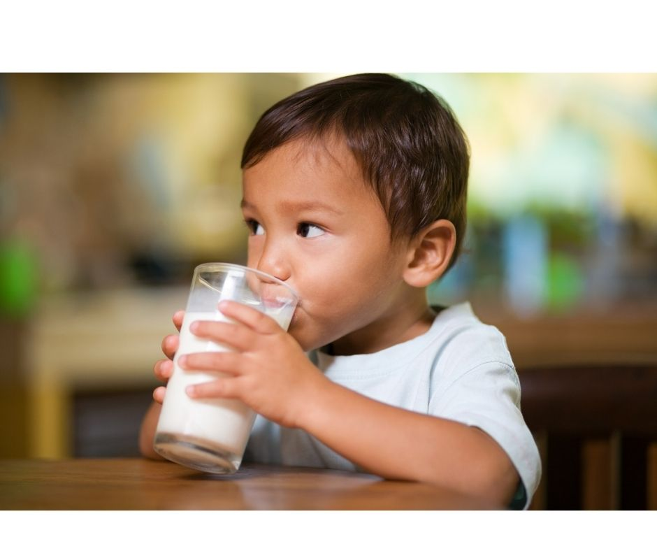 Little boy drinking a glass of dairy